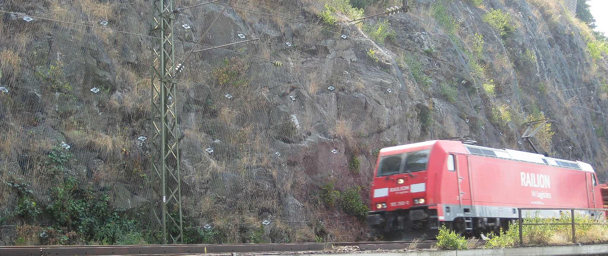 Train and rockface stabilized with TECCO® mesh